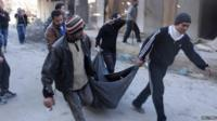 The body of a man believed to have been executed by Islamist State in Iraq and the Levant (ISIS) is carried through Aleppo (8 January 2014)