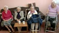 Residents of care home sit on sofa