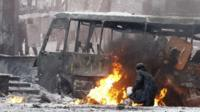Protesters take cover behind a burnt bus during clashes in Kiev