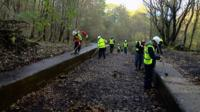 People clearing a disused canal lock
