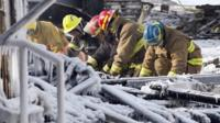 Rescue personnel search through the icy rubble