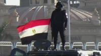Egyptian police officer stands on armoured vehicle
