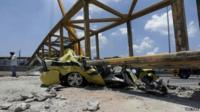 Crushed yellow taxi under collapsed bridge in Rio de Janeiro