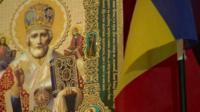 Religious icon and Romanian flag
