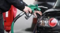 A person using petrol pump at a petrol station