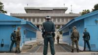 South Korean soldiers look towards the North Korean side as a North Korean solder approaches the UN truce village building that sits on the border of the Demilitarized Zone (DMZ) in Panmunjom, South Korea, on 30 September 2013