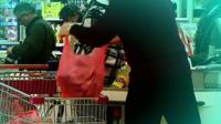 Shopper loading supermarket trolley