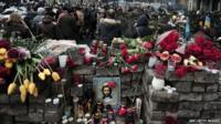People walk by barrycades and makeshift memorials to the victims of the riots in central Kiev
