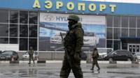 Armed men patrol outside of Simferopol airport, on February 28, 2014