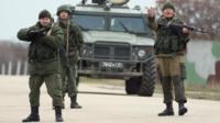 Troops under Russian command scream orders to turn back before firing weapons into the air