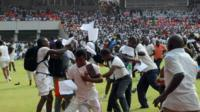Jobseekers scramble as their exam papers fly in the air, on the pitch of Abuja National Stadium, Nigeria