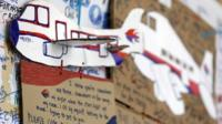 A message card is seen below a paper plane of a Malaysian airliner, on the message board for passengers aboard a missing Malaysia Airlines plane at Kuala Lumpur International Airport