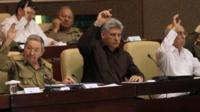 Cuban lawmakers with their hands in the air