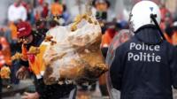 demonstrator throws garbage towards riot police officers during a European trade unions protest against austerity measures, in central Brussels April 4, 2014