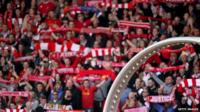 Fans holding football scarves and wheel showing names of the 96 dead