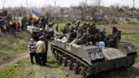 Ukrainian soldiers sit on top of armoured personnel carriers while surrounded by pro-Russia protesters in Kramatorsk
