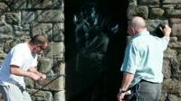 The Banksy being removed by two men