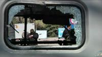 Armed men can be seen through a smashed window