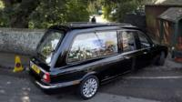 A hearse carrying the coffin of Peaches Geldof, painted with a picture of her family, arrives at church
