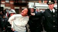 Still of someone having the hair grabbed by a NY police person