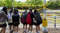 School children hang yellow ribbons by a road side at the main gate of Danwon high school