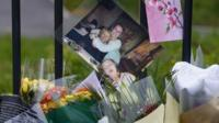 A photograph of teacher Ann Maguire (L) who was fatally stabbed sits with floral tributes outside Corpus Christi Catholic College in Leeds