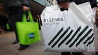 A shopper with a John Lewis bag