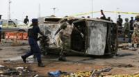 Two men move part of a damaged car at the scene of a car bomb attack in Abuja, May 2, 2014.