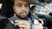 Constable Yasa Amerat (left) and Constable Craig Pearson pictured in their police car wearing body-worn video (BWV) cameras