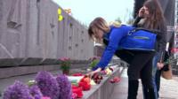 Girl laying flowers at memorial