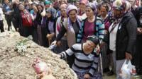 Women mourn at a cemetery in Soma, Turkey, during the funeral of a miner who died in a fire at a coal mine on Tuesday
