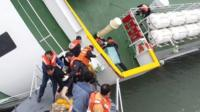 """This screen grab taken from a video released by Korea Coast Guard on April 28, 2014 shows the sunken South Korean ferry """"Sewol"""" captain Lee Joon-Seok (L), wearing a sweater and underpants, being rescued from the tilting vessel"""