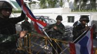 Thai soldiers hold national flags as they dismantle an anti-government encampment in central Bangkok