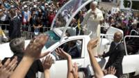 Pope Francis waves to the crowd, from his pope-mobile