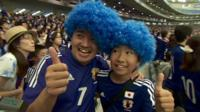 Man and boy in blue wigs and Japan strips