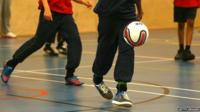 Children playing football in a school gym