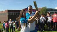 Student hands Queen's Baton to teacher Bob Foley at Newbattle High School