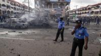 Policemen walk towards burnt vehicles at the scene of a blast at a business district in Abuja