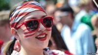 US soccer fan, wearing sunglasses, is smiling