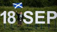 """A man holding a Saltire flag stands next to giant letters which says """"18 Sep""""."""
