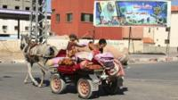 Palestinians ride a horse and cart in front of a billboard depicting late Hamas leaders, in the northern Gaza Strip, 14 July 2014