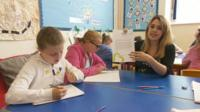 Reporter holding letter in classroom with pupils