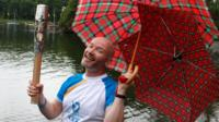 Craig Hill carries the Glasgow 2014 Queen's Baton through Bardowie in East Dunbartonshire.