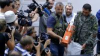 Rebel fighters unveil the flight-data recorders at a meeting with Malaysian officials in Donetsk