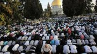 "Muslim worshippers take part in a prayer in front of the Dome of the Rock during the holiday of Eid al-Fitr on the compound known to Muslims as al-Haram al-Sharif and to Jews as Temple Mount in Jerusalem""s Old City"