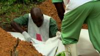 Four-month-old Ebola victim from the affected village of Gueckedou, Guinea, is buried by aid workers