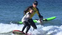 man teaching girl to surf