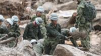 Defence personnel search for victims in mud after a landslide hit an area in Hiroshima