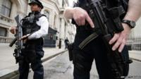 Armed police officers hold guns