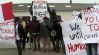 A group of migrants holding placards